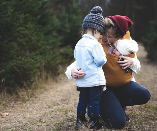 woman-with-brown-baby-carrier-and-little-kid-in-white-jacket-701014